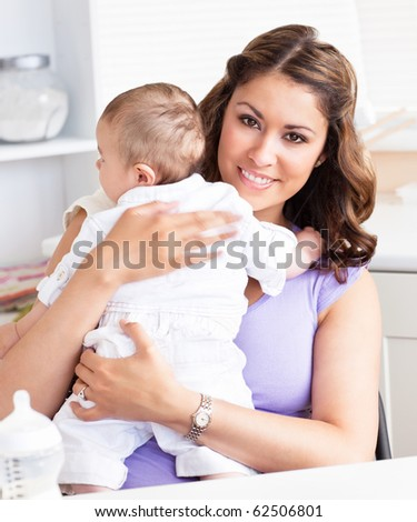 Smiling young mother holding her baby in her arms - stock photo