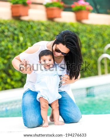 With baby boy near the swimming pool on a sunny day stock photo
