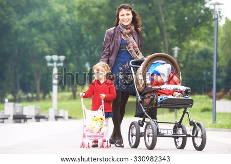 Smiling young mother walking with daughter outdoors in a spring park pushing pram. Little boy in stroller. - stock photo