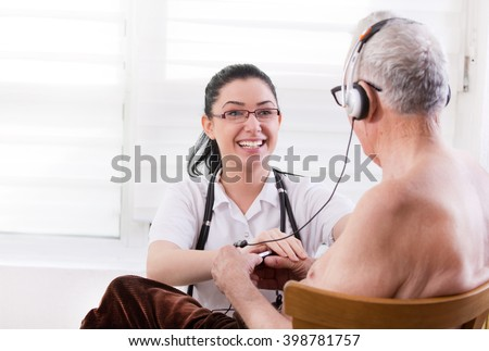 Smiling young nurse taking care about senior man with headset - stock photo