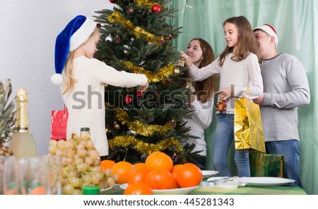Smiling young parents and two little daughters decorating Christmas tree together at home. Selective focus - stock photo