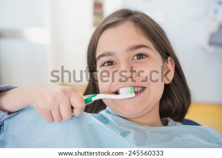 Smiling young patient holding touthbrush in dental clinic - stock photo