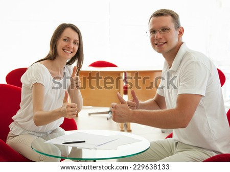 Smiling young people  holding their thumbs up on workplace - stock photo