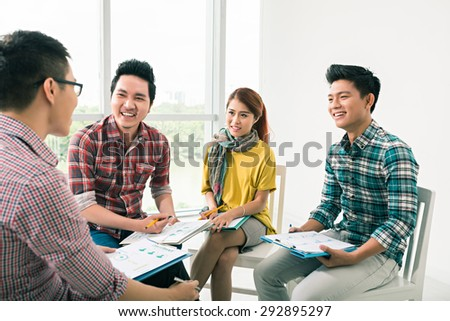 Smiling young people listening to their colleague at business meeting - stock photo