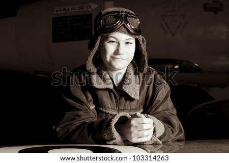 Smiling young pilot with goggles resting on airplane wing, smiling at the camera - stock photo