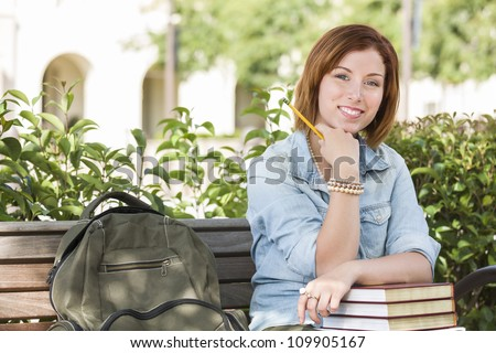 Smiling Young Pretty Female Student Outside on Campus with Backpack and Books Sitting on Bench. - stock photo