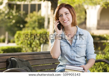 Smiling Young Pretty Female Student Outside on Cell Phone with Backpack and Books Sitting on Bench. - stock photo