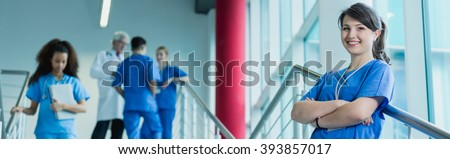 Smiling young pretty girl in scrubs standing on hospital stairs. In the background busy colleagues talking with professor - stock photo