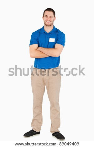 Smiling young salesman with arms folded against a white background - stock photo