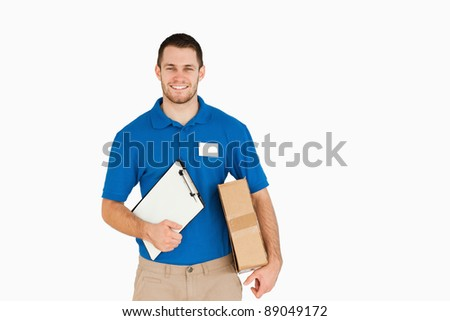 Smiling young salesman with parcel and clipboard against a white background - stock photo