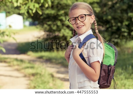 Smiling young school child in a school uniform standing against a tree in the park at the day time. Concept of the child are ready to go to school. - stock photo