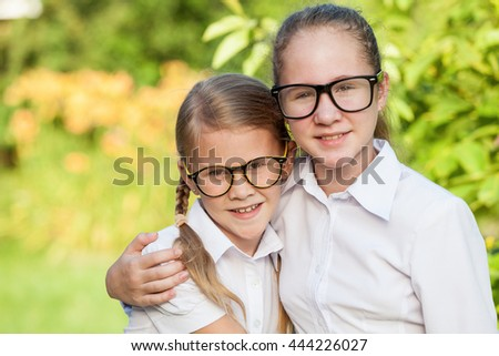 Smiling young school children in a school uniform standing against a tree in the park at the day time. Concept of the children are ready to go to school. - stock photo