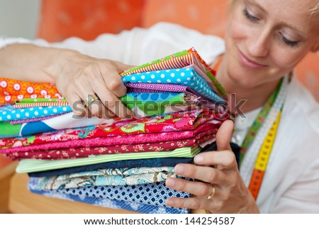 Smiling young seamstress bending down choosing a fabric from a pile of neatly folded examples for use in making modern clothing - stock photo