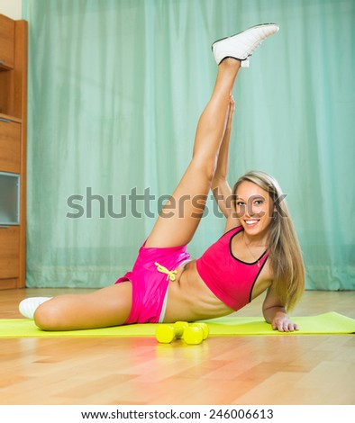 Smiling young slender woman working out with dumbbells at home - stock photo