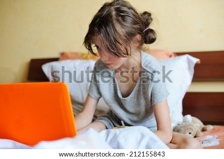 Smiling young teenager lying on her bed and using a laptop - stock photo
