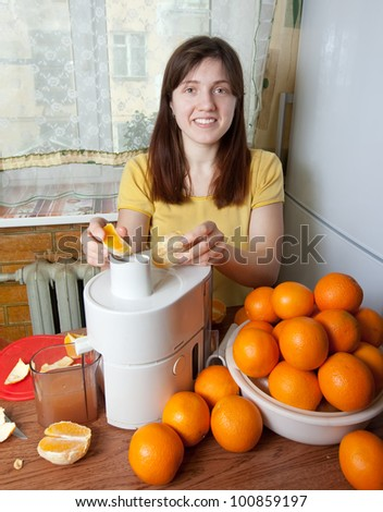 smiling young  woman adding orange to juicer in her kitchen - stock photo