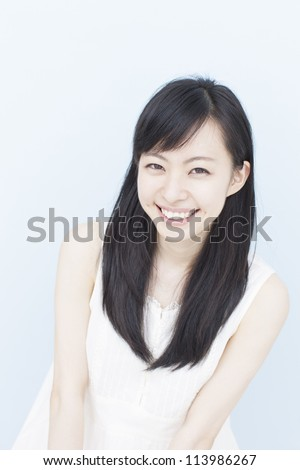 smiling young woman against pale blue background - stock photo