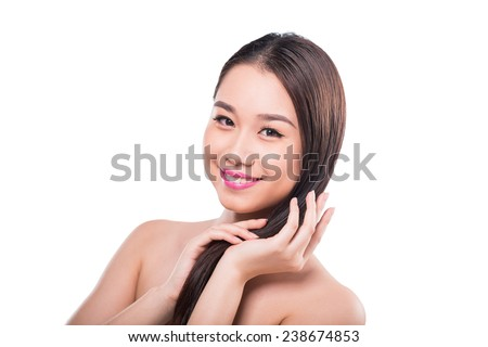 Smiling young woman applying conditioner - stock photo
