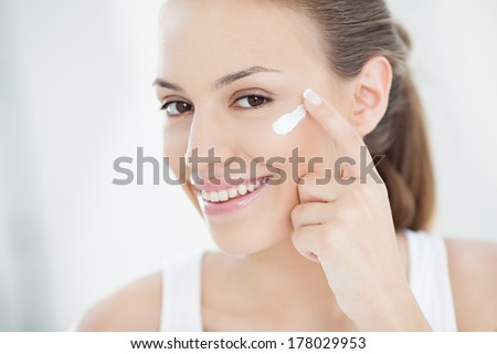 Smiling young woman applying face cream. - stock photo