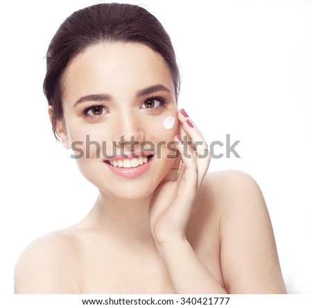 Smiling young woman applying face cream - stock photo