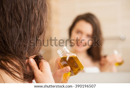 Smiling young woman applying oil mask to hair tips in front of a mirror; haircare concept - stock photo