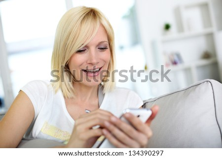 Smiling young woman at home using smartphone - stock photo