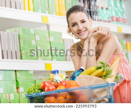 Smiling young woman at supermarket with full shopping basket. - stock photo
