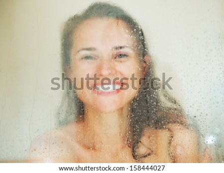 Smiling young woman behind weeping glass shower door - stock photo