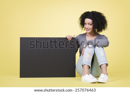 Smiling young woman being joyful  holding a black paper sign board with copy space. - stock photo