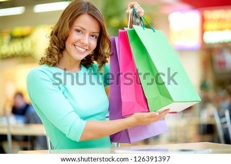 Smiling young woman boasting of her purchases - stock photo