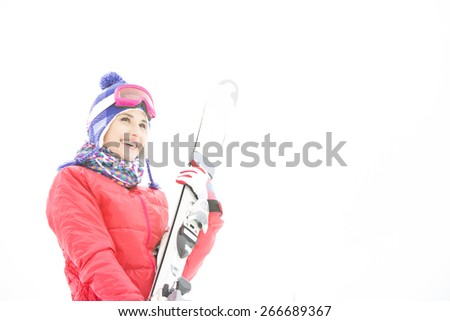 Smiling young woman carrying skis in snow - stock photo