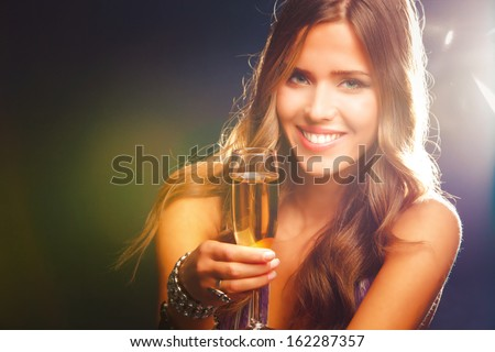 smiling young woman celebrating with champagne - stock photo