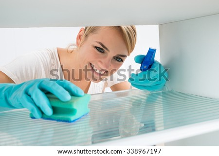 Smiling young woman cleaning refrigerator with sponge and spray at home - stock photo
