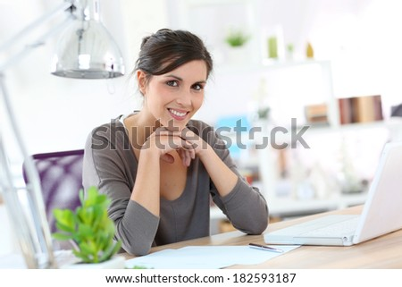 Smiling young woman designer working on laptop - stock photo