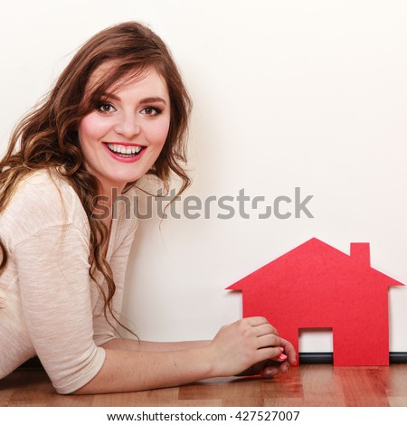 Smiling young woman girl holding paper house dreaming about new home. Housing and real estate concept. - stock photo