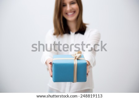 Smiling young woman giving gift. Focus on a gift - stock photo
