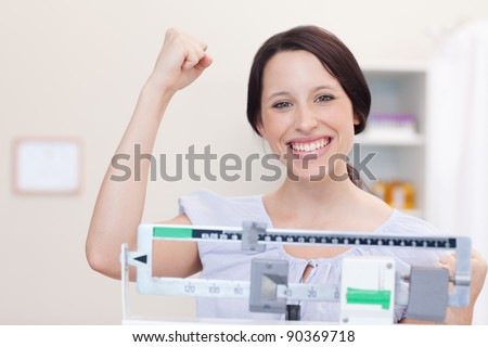Smiling young woman happy about what the scale shows - stock photo