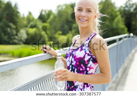 Smiling young woman having her break after running - stock photo