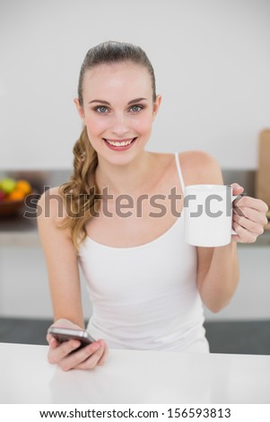 Smiling young woman holding a mug and texting with smartphone in the kitchen at home - stock photo