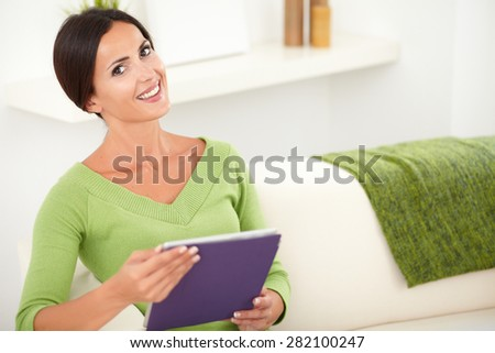 Smiling young woman holding a tablet while sitting inside the house - copy space - stock photo