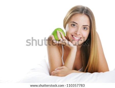 Smiling Young Woman Holding Apple in Bed - stock photo