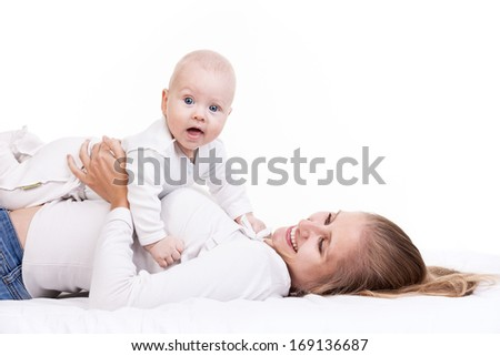 Smiling young woman holding baby son while lying on back  - stock photo