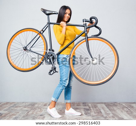 Smiling young woman holding bicycle on shoulder on gray background. Looking at camera - stock photo