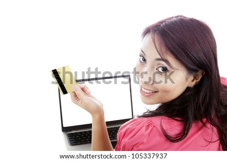 Smiling young woman holding credit card for online shopping with laptop isolated on white - stock photo