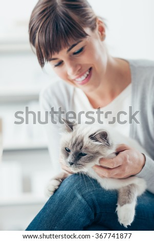 Smiling young woman holding her cat on her legs and cuddling it, pet care and togetherness concept - stock photo