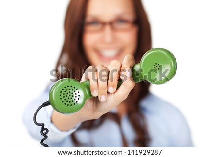 Smiling young woman holding out a green telephone handset in her extended hand offering it to the viewer with shallow dof - stock photo