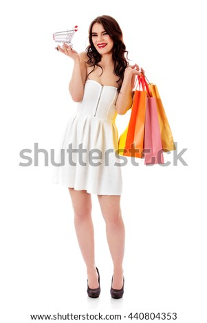 Smiling young woman holding small empty shopping cart and shopping bags - stock photo