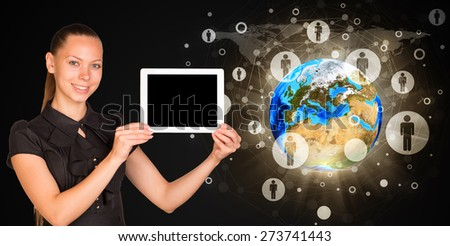 Smiling young woman holging tablet looking at camera. Model of earth on black background. Connection all over the world. Elements of this image furnished by NASA - stock photo