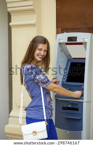 Smiling young woman in a blue blouse withdrawing money from ATM - stock photo
