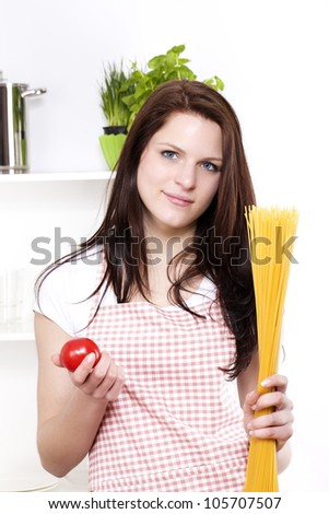 smiling young woman in a kitchen holding spaghetti and tomato - stock photo